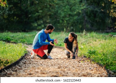 Handsome caucasian man crouching ant talking to his female friend while she crouching and tying shoelace. Both are dress in sportswear. Fitness in nature concept.