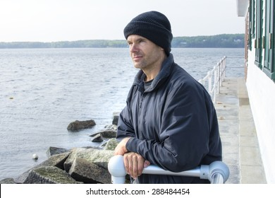 Handsome Caucasian man dressed in jacket and black cap leans against railing of lighthouse at end of breakwater in Rockland, Maine as he gazes peacefully into the distant ocean