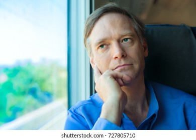 Handsome Caucasian man in early fifties looking out train window, thinking while resting head on hand. Commuting businessman, thinking on train