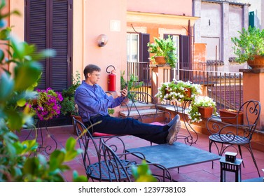 Handsome Caucasian man in forties relaxing outdoors on red terracota Italian  veranda with legs up on table, looking at smartphone