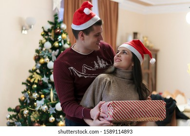 Handsome caucasian man giving christmas present to his loving girlfriend. Woman smile and thanking man for gift. Both are dressed in sweaters and having santa hat on heads. Christmas holiday.