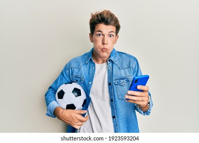 Handsome caucasian man holding football ball looking at smartphone puffing cheeks with funny face. mouth inflated with air, catching air.