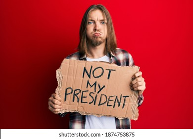 Handsome caucasian man with long hair holding not my president protest banner puffing cheeks with funny face. mouth inflated with air, catching air.