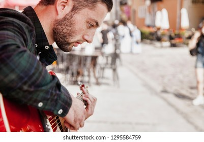 Handsome caucasian man playing the guitar outdoors. Music, art, creativity concept.