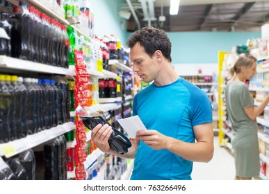 Handsome caucasian man shopping in a supermarket. Man carefully reading nutrients of bottle with beverage