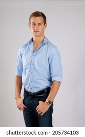 Handsome Caucasian man standing with his thumbs in his pockets, looking seriously at the camera