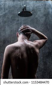 Handsome caucasian man taking a rain shower