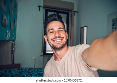 Handsome caucasian man taking a self portrait indoor at home