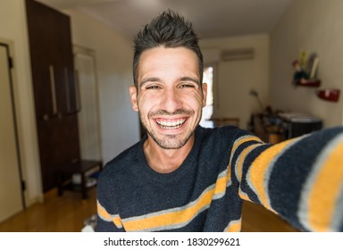 Handsome caucasian man taking a selfie portrait indoor at home - Happy guy smiling at the camera.
