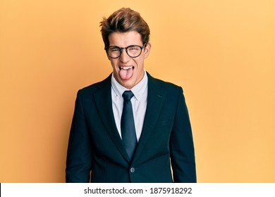 Handsome caucasian man wearing business suit and tie sticking tongue out happy with funny expression. emotion concept.