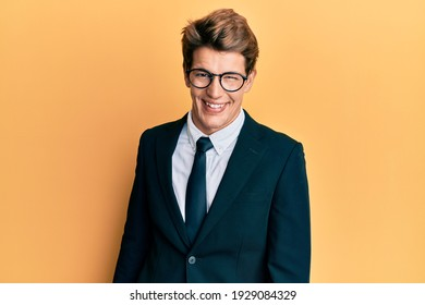Handsome caucasian man wearing business suit and tie winking looking at the camera with sexy expression, cheerful and happy face.