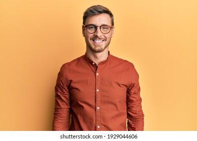 Un bel homme caucasien portant des vêtements et des lunettes décontractés avec un sourire joyeux et frais sur le visage. chanceux.