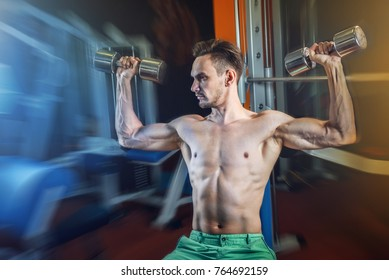 Handsome caucasian man working out at gym and doing shoulders exercises with dumbells.