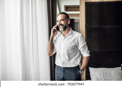 Handsome Caucasian middle-aged businessman standing at bedroom and talking on mobile phone.