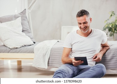 Handsome Caucasian middle-aged man sitting on the floor in bedroom and leaning on bed. In hands tablet.