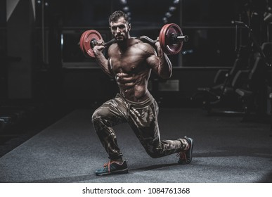 Handsome caucasian muscle man model appearance workout in gym training legs quadriceps and hamstrings on machines and with a barbell pumping up and poses fitness bodybuilding and sport nutrition