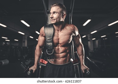 Handsome caucasian muscular man on diet in the gym after execute exercise. Brutal bodybuilder powerful training arms, pectorals and shoulders