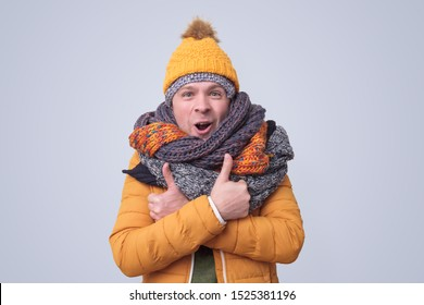 Handsome caucasian shocked funny man in several hats and scarfs showing thumb up gesture on colored background. Winter fashion.
