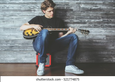 Handsome caucasian teenager with electric guitar sitting on amplifier in wooden room. Music, concert rehearsal concept