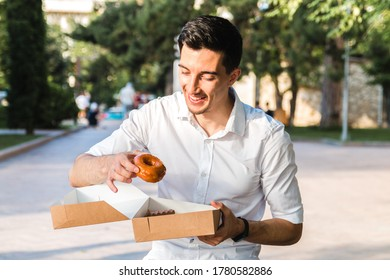 handsome caucasian young man in white shirt enjoying delicious caramel donut in city park. junk but tasty food for positive thinking