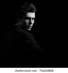 Handsome charismatic man looking serious in dark shadow dramatic light. Black and white portrait. Art