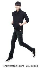 Handsome, charming, young Chinese man running, jogging and jumping. Focus on eyes and face. Intentional motion blur with his left leg to give a sense of movement.