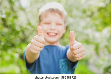 Handsome cheerful 9 years old boy showing two hands with thumbs up into camera as symbol of success. Closeup of fingers with focus at them, blurry face of blonde cute happy kid dressed in casual wear