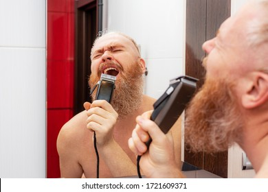 Handsome cheerful bearded man singing into hair trimmer instead of microphone in front of mirror in bathroom at home. Positive happy man joking and portraying a singer. Closeup
