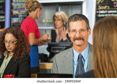 Handsome cheerful businessman talking sitting in cafeteria