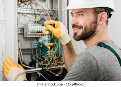 handsome cheerful electrician repairing electrical box and using screwdriver in corridor