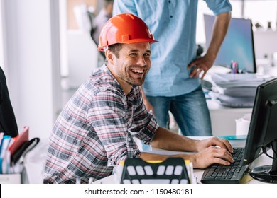 handsome cheerful engineer is having fun in front of the computer at work. happiness concept