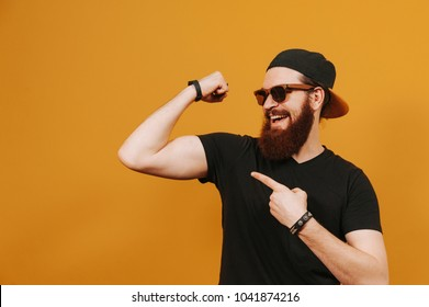 Handsome cheerful hipster man in cap and sunglasses showing bicep having fun in studio.