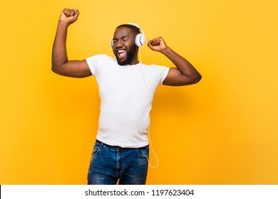 Handsome cheerful man in ear phones wearing white t-shirt and jeans dancing, singing, isolated over bright vivid yellow background