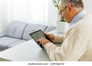 Handsome cheerful senior man using digital tablet sitting at the table in the living room. Leisure activities, spending time, happy retirement and senior lifestyle concept