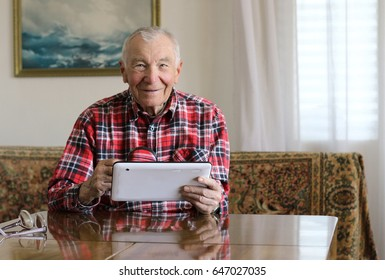 Handsome cheerful senior man using digital tablet sitting at the table in the living room. Leisure activities, spending time, happy retirement and senior lifestyle concept.