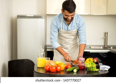 Handsome cheerful smiling indian man cooking summer salad for dinner, cutting tomato on chopping board, preparing dinner for wife at home in the kitchen. Healthy food, cooking concept.