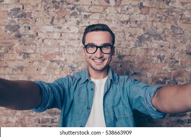 Handsome cheerful smiling man in glasses making selfie