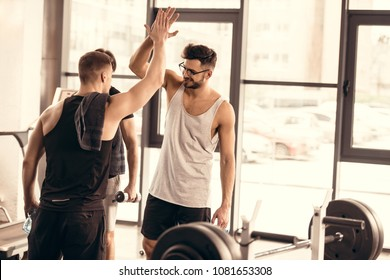handsome cheerful sportsmen giving high five in gym
