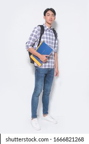 Handsome cheerful student holding book in hands and standing with backpack isolated on white background
