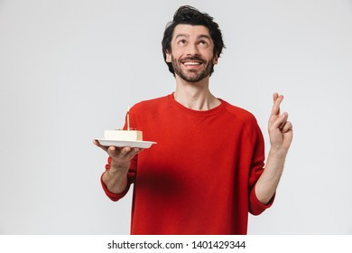 Handsome cheerful young bearded brunette man wearing sweater standing isolated over white background, holding plate with piece of birthday cake with candle, fingers crossed