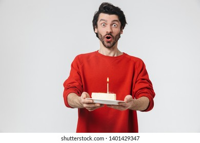 Handsome cheerful young bearded brunette man wearing sweater standing isolated over white background, holding plate with piece of birthday cake with candle