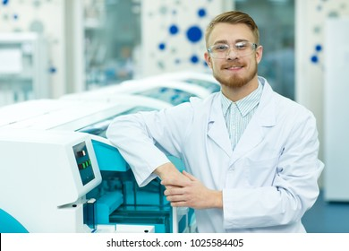 Handsome cheerful young male scientist smiling joyfully to the camera posing at the modern laboratory copyspace equipment research technology machines biology chemistry medicine healthcare profession.
