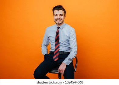 Handsome cheerful young man in casual sitting on chair smiling and looking at the camera over orange background.