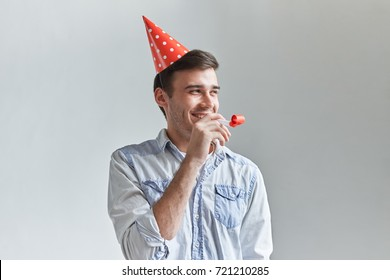 Handsome cheerful young man with dimpled smile having fun on party wearing blue denim shirt and red holiday hat, blowing party horn and laughing. People, joy, birthday and celebration concept
