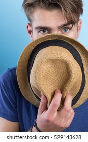 Handsome cheerful young man in hat against blue background