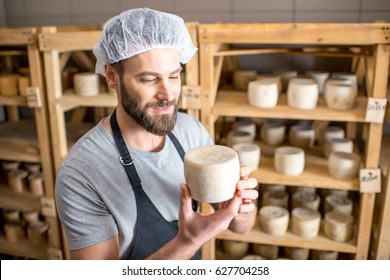 Handsome cheese maker checking the aging process of the goat cheese standing at the small cellar