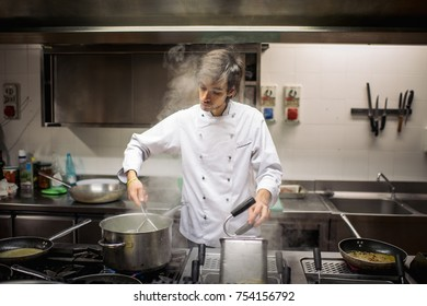 Handsome chef cook in uniform cooking food on the gas stove at the restaurant kitchen