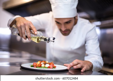 Handsome chef pouring olive oil on meal in a commercial kitchen