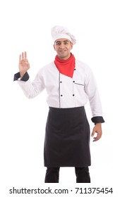 Handsome chef smiling and rising his hand, guy wearing a chef uniform and chef hat against white background