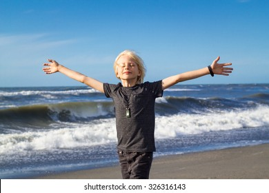 Handsome child at beach, arms outstretched in freedom concept